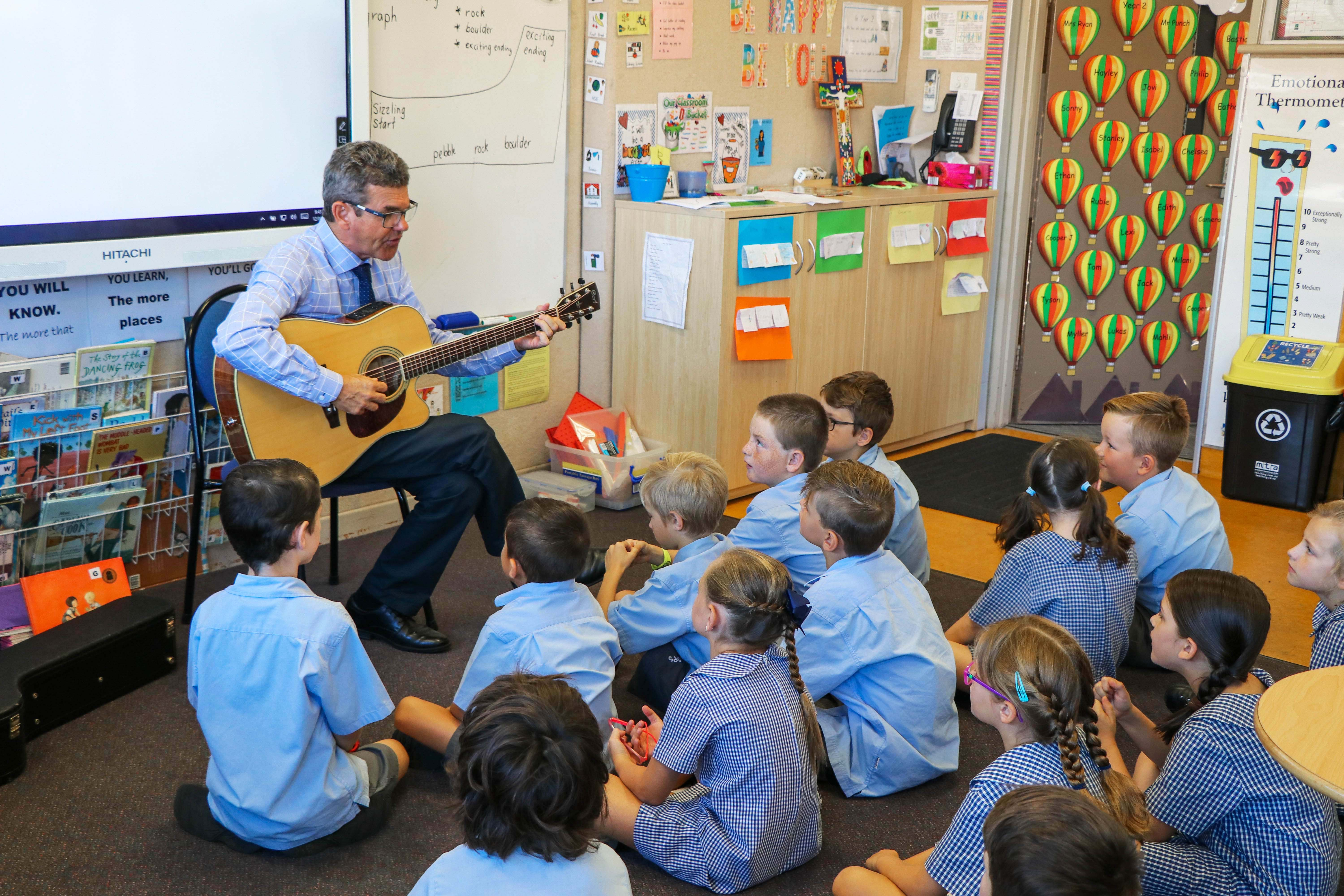 teacher playing guitar in front of students